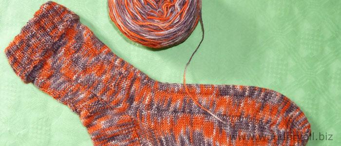 Das selbstgefärbte Wollknäuel und der fertige Socken